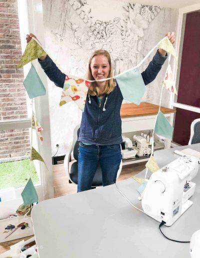 Ivrouw-houd-een-vlaggenlijn-omhoog-achter-de-naaimachine-die-ze-gemaakt-heeft-tijdens-de-naaicursus-bij-Naaistudio-6