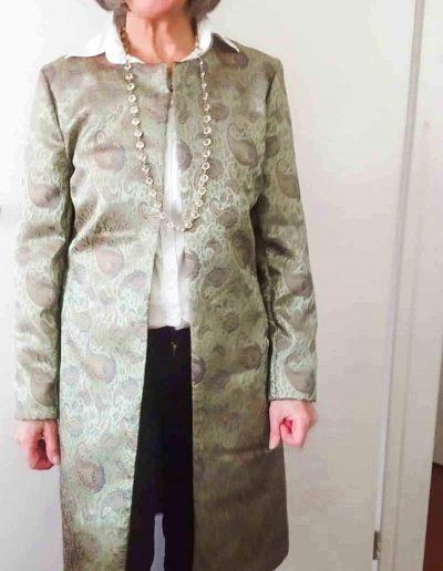 vrouw-lacht-en-is-blij-met-haar-groene-vest-die-ze-zelf-gemaakt-heeft-tijdens-de-naaicursus