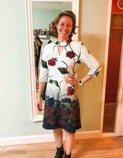 vrouw-staat-voor-een-spiegel-en-draagt-een-tricot-witte-jurk-met-rode-rozen-die-ze-zelf-gemaakt-heeft-tijdens-de-naaicursus